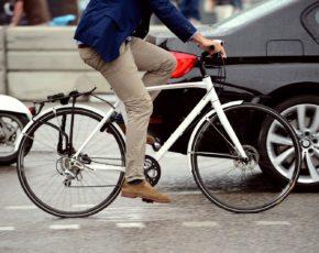 Homem andando de bicicleta com carros ao fundo
