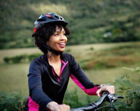 Mulher sorrindo andando de bicicleta com capacete
