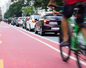 Ciclista na ciclofaixa e carros em segundo plano