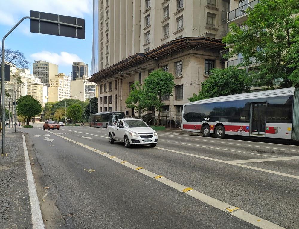 Automóveis circulando nas ruas com prédios no fundo